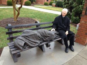 Rev. David Buck sits next to the Jesus the Homeless statue that was installed in front of his church, St. Alban's Episcopal, in Davidscon, N.C.
